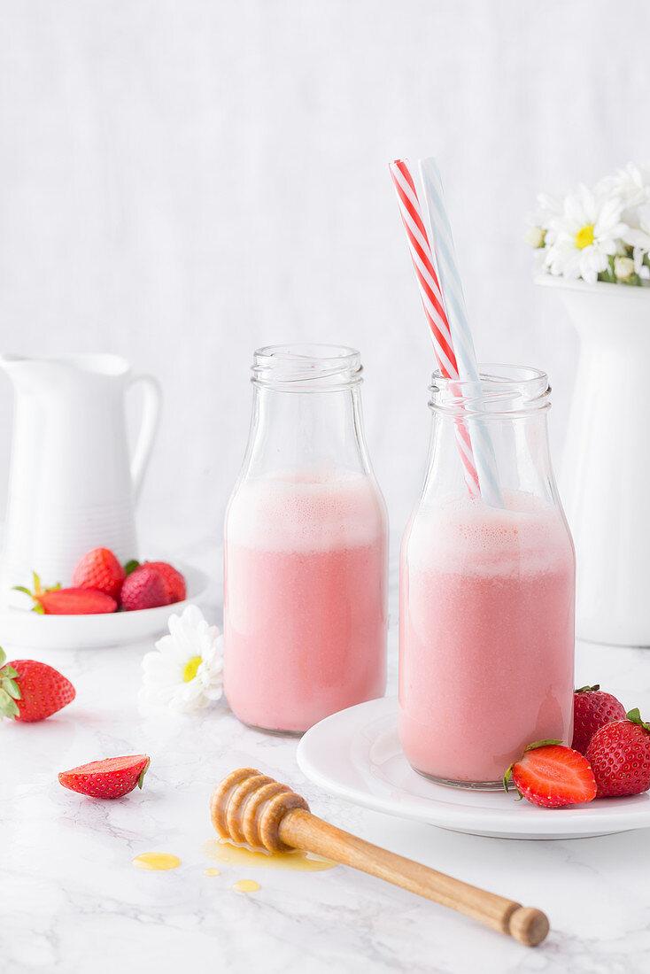 Pink strawberry milkshake served in bottles with straw