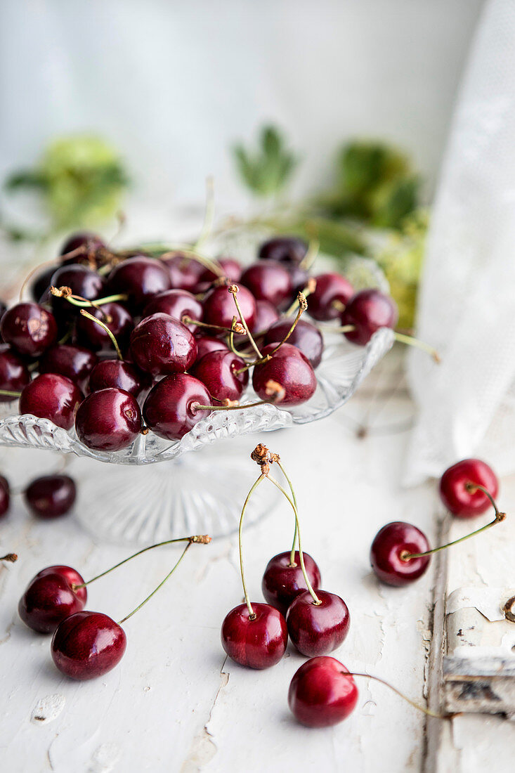 Fresh cherries in a crystal bowl by a kitchen window
