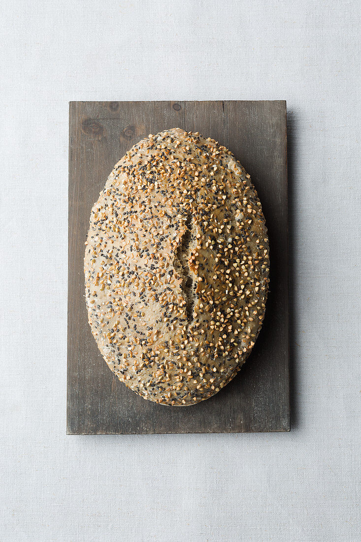 A loaf of light seeded bread on a wooden board