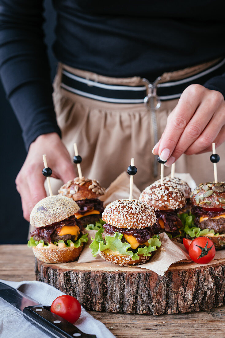 Hands putting small burgers on a wooden plate