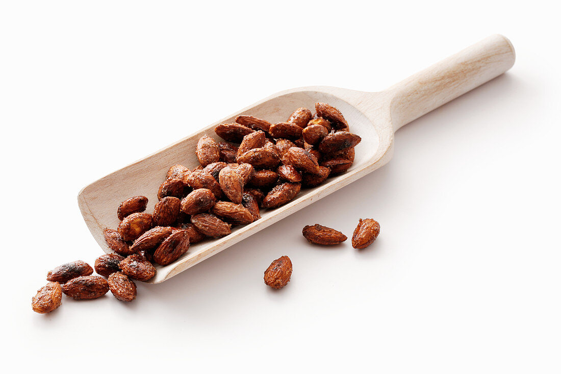 Roasted almonds on a wooden scoop