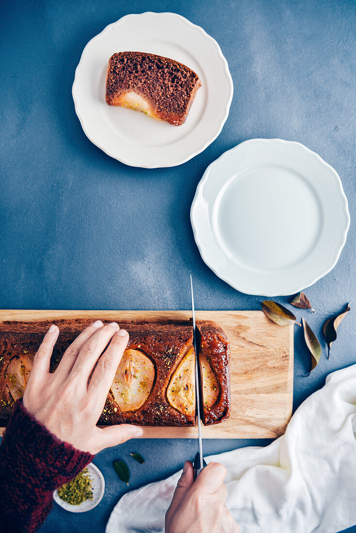 Hands slicing a pear loaf cake on a wooden board
