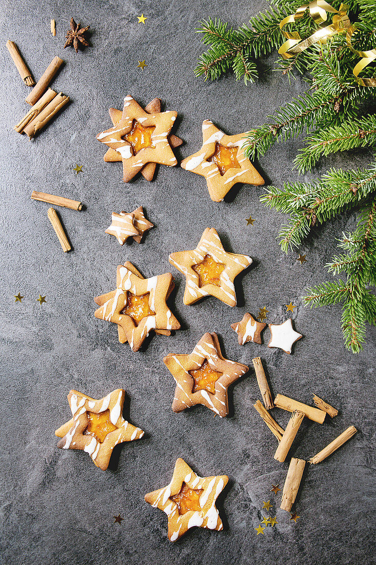 Homemade Christmas New year star shape sugar caramel cookies with frosting and orange citrus jam, cinnamon sticks and anise