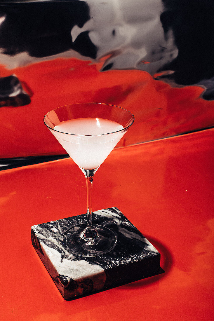 A margarita on a marble plate in front of a red background