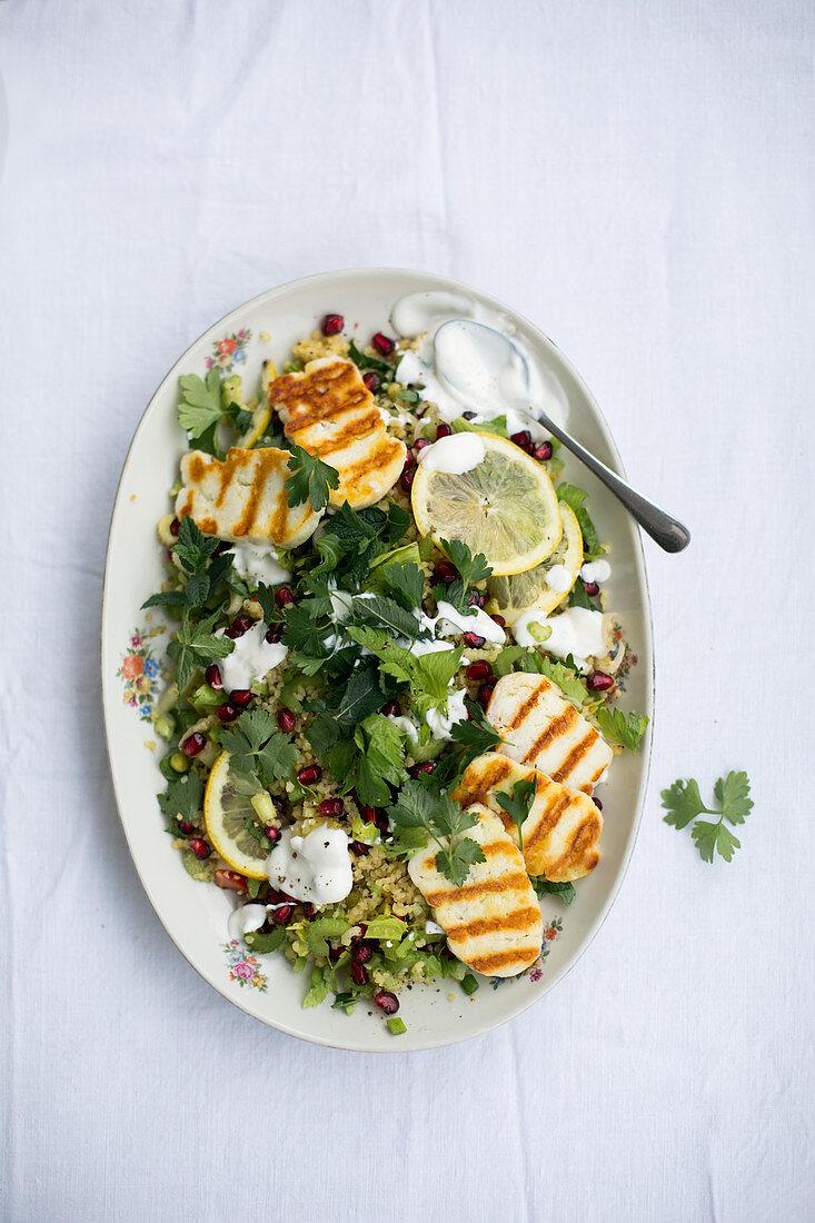 Bulgur salad with grilled halloumi, pomegranate seeds, celery, parsley and a yoghurt dip