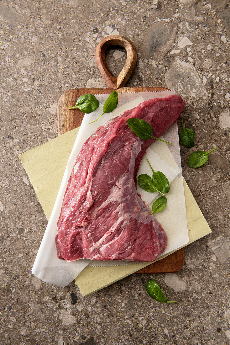 Beef breast with baby spinach leaves on parchment paper