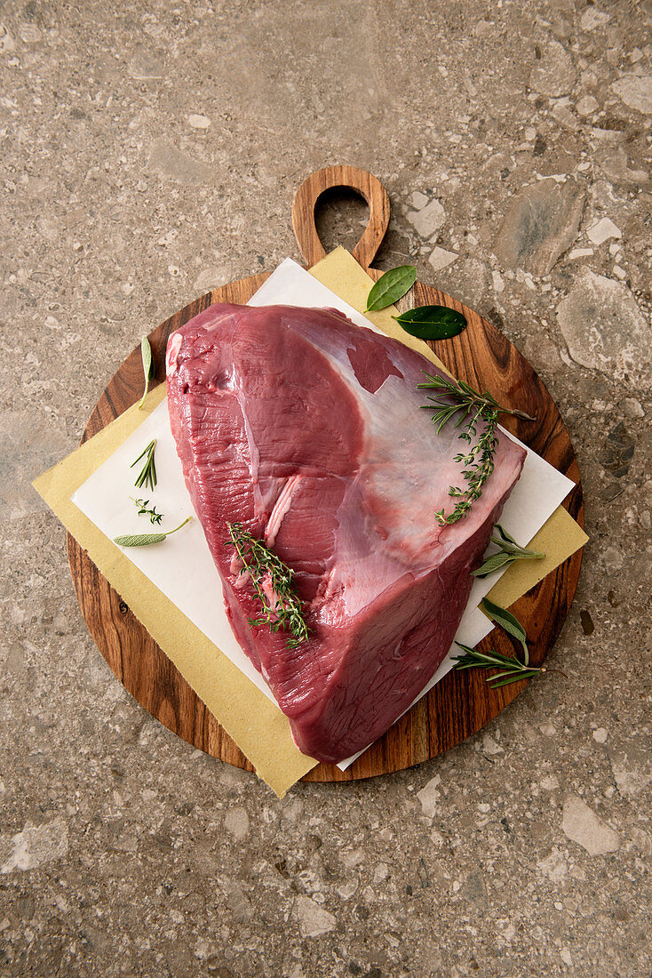 Ox leg with herbs on a wooden chopping board