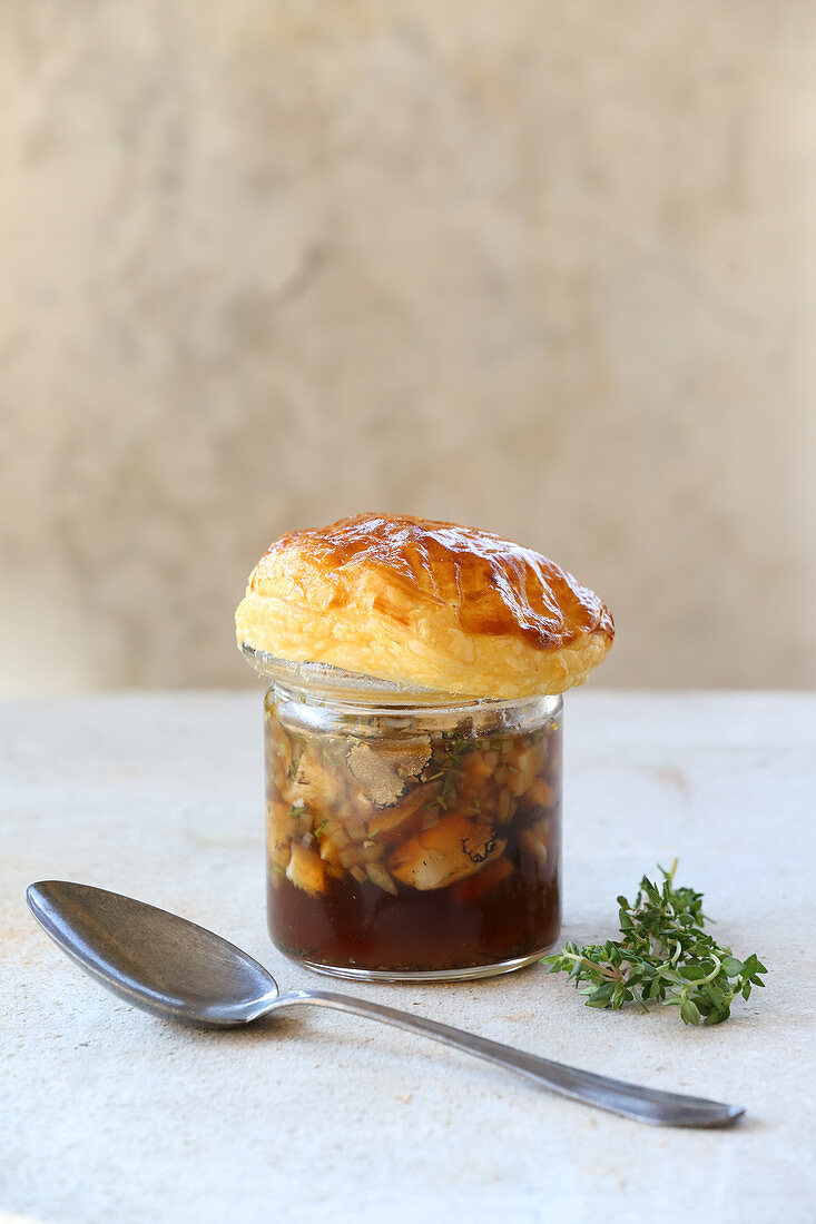 Mushroom broth with a puff pastry topping in a glass