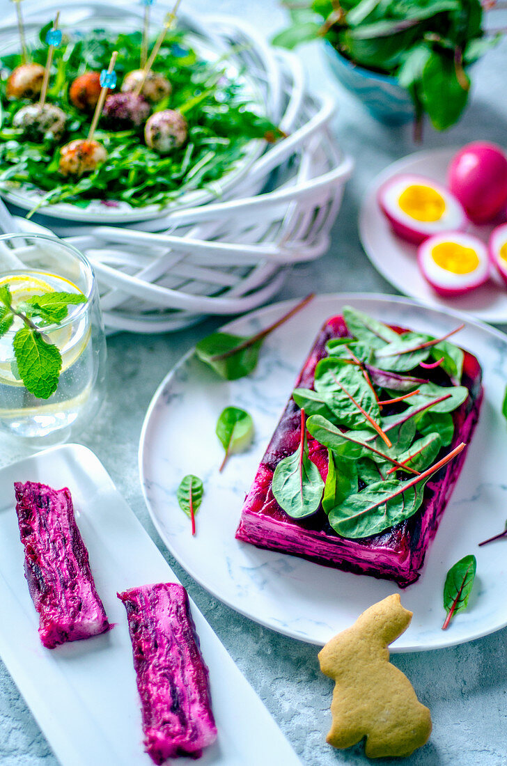 Easter terrine with beetroot and goat cheese, chicken eggs, painted beet juice, quail eggs