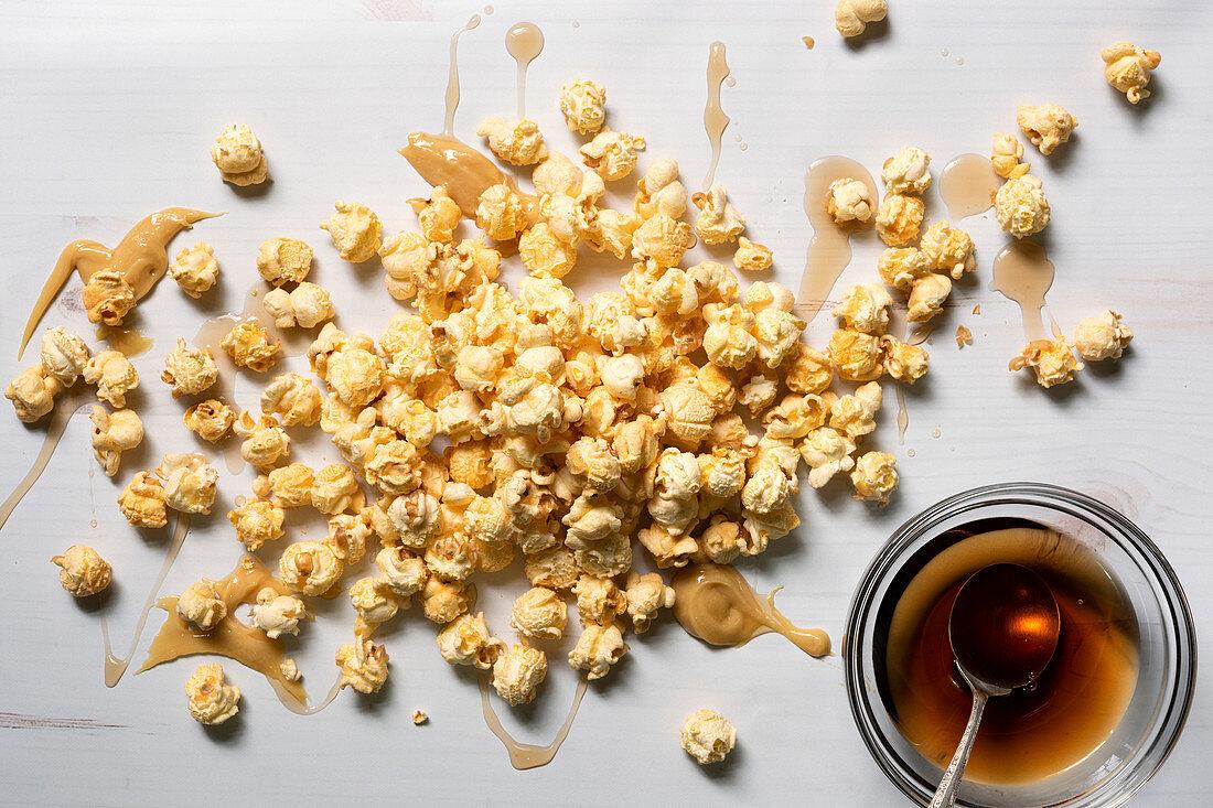 Ahornbutter-Popcorn beträufelt mit Ahornsirup (Aufsicht)
