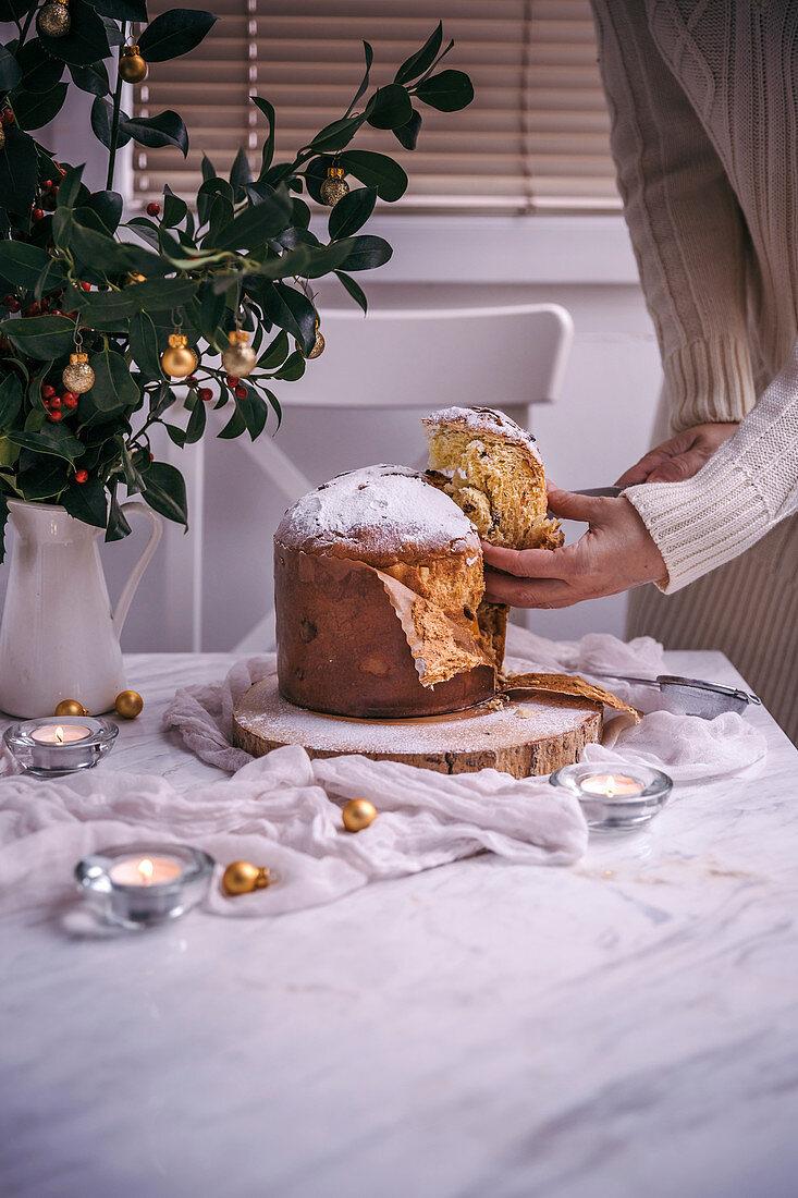 Woman slicing Panettone Christmas cake