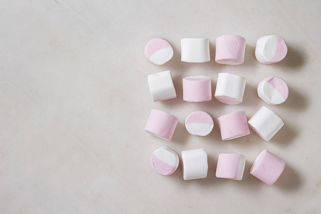 White pink big marshmallow in row over white marble background