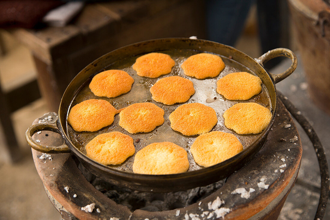 Many egg cakes in a brass pan on an ancient charcoal stove, Samut Songhkram, Thailand