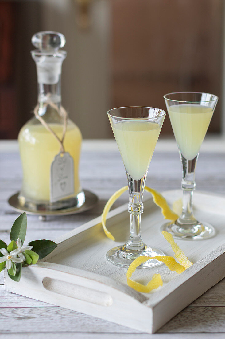 Limoncello in a carafe and two glasses on a wooden tray