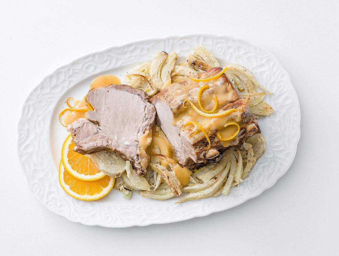Roast pork with orange sauce on a bed of fennel vegetables