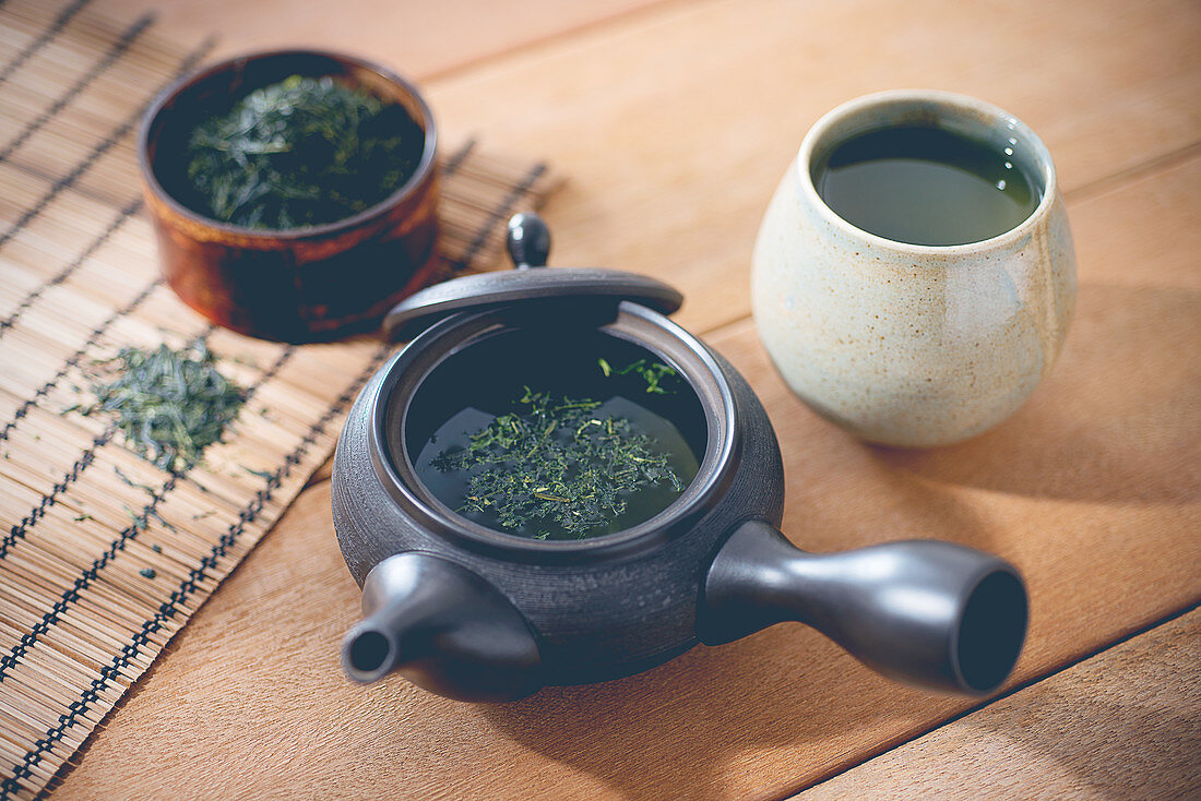 Green tea in a pot and a mug