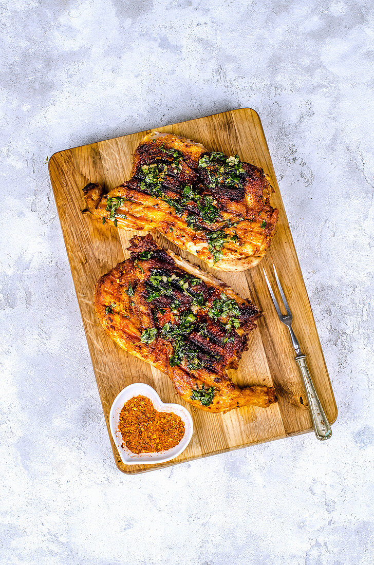 Chicken Tabaka with spices and herbs with garlic on a wooden board
