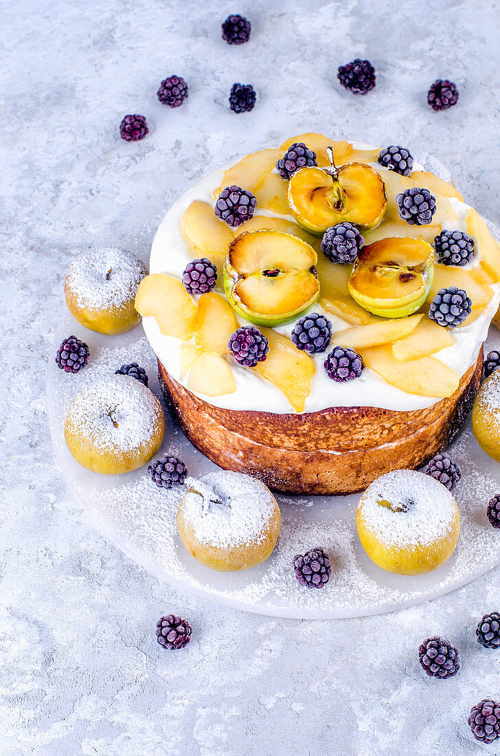 Biscuit cake with cream and caramelized apples with blackberries on a marble stand decorated with fresh apples with icing sugar