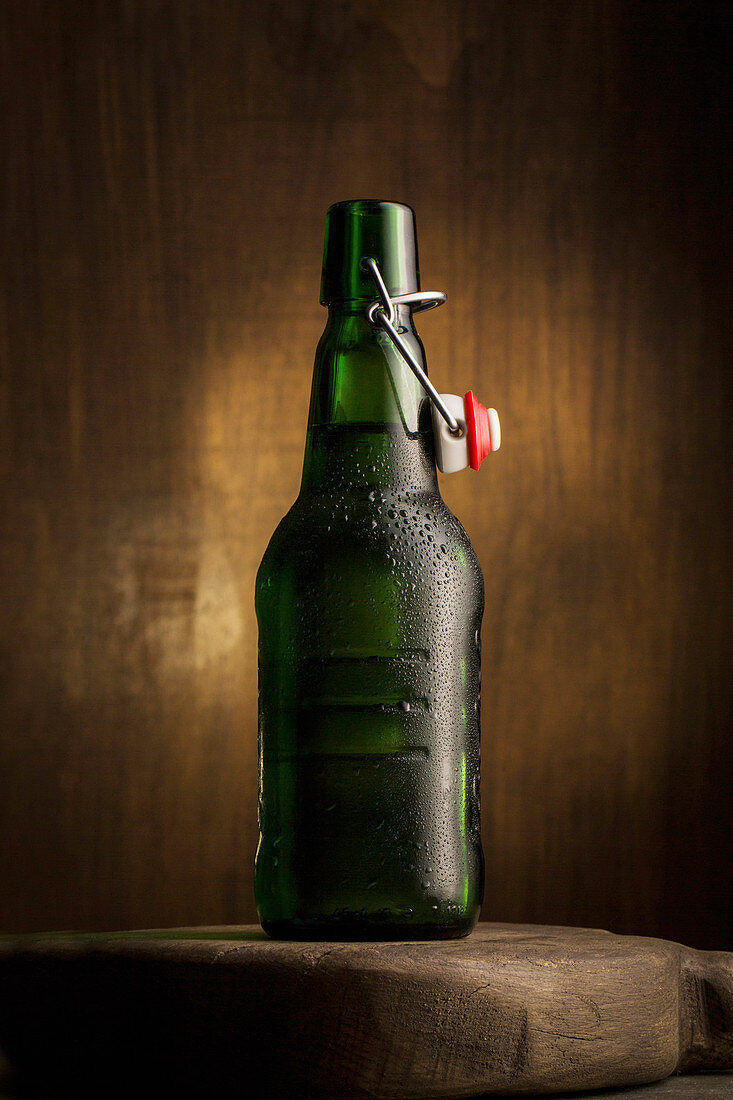 An open bottle of beer on a wooden board