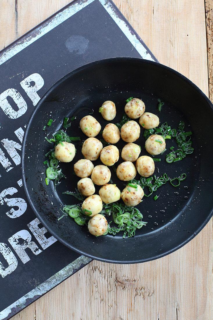 Mini potato dumplings with roast onions in a pan