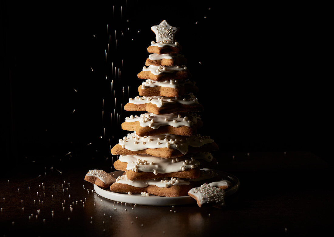 A Christmas tree made from different sized star-shaped biscuits with icing
