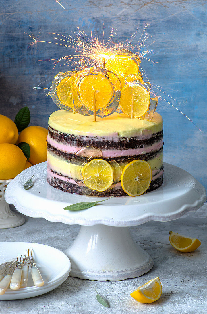Chocolate naked cake with pink and yellow cream, decorated with candy with slices of lemons and sparklers