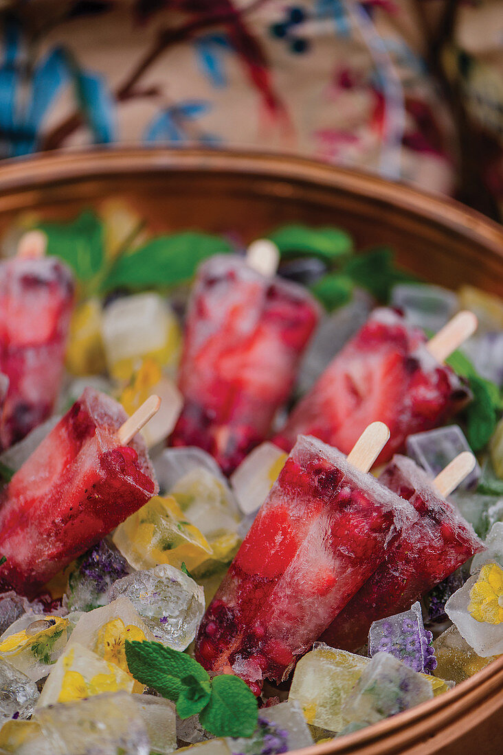 Champagne and berry popsicles on edible flower ice cubes