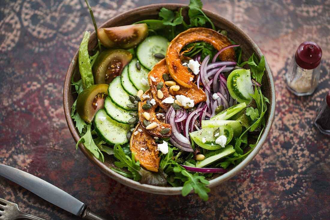 A salad bowl with rocket, cucumber, butternut squash, tomato, red onion, pine nuts and goat's cheese