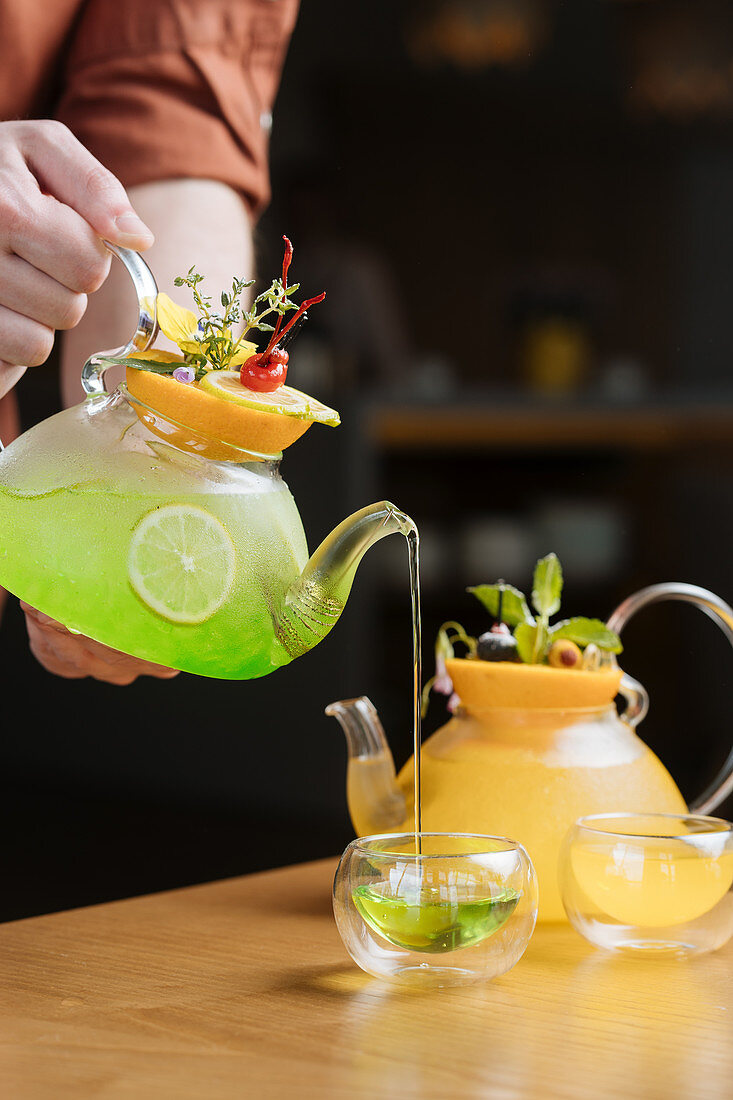 A person pouring a cocktail from a glass jug into a drinking cup