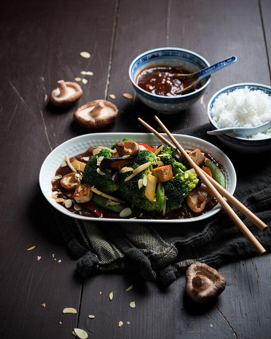 Vegan vegetables with Sichuan sauce, fried tofu, shiitake mushrooms and rice (Asia)