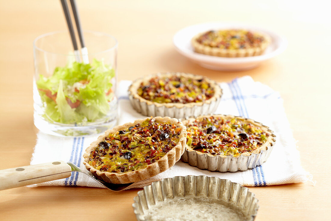 Roman lentil tartlets with shortcrust pastry, leeks, carrots, bacon, olives and egg