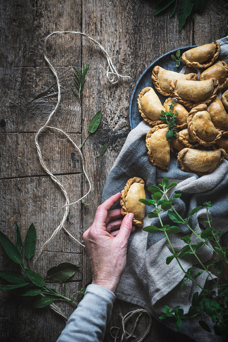 Baked pies with golden crust on textile with green above wooden table
