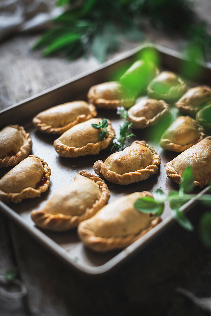 Baking tray with composed freshly baked pies having golden crispy crust and garnishes with green