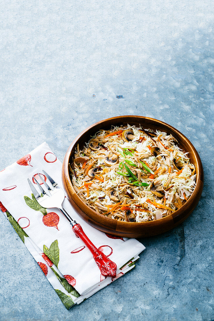 Asian egg roll cabbage salad bowl with carrots and mushrooms, topped with sliced green onions