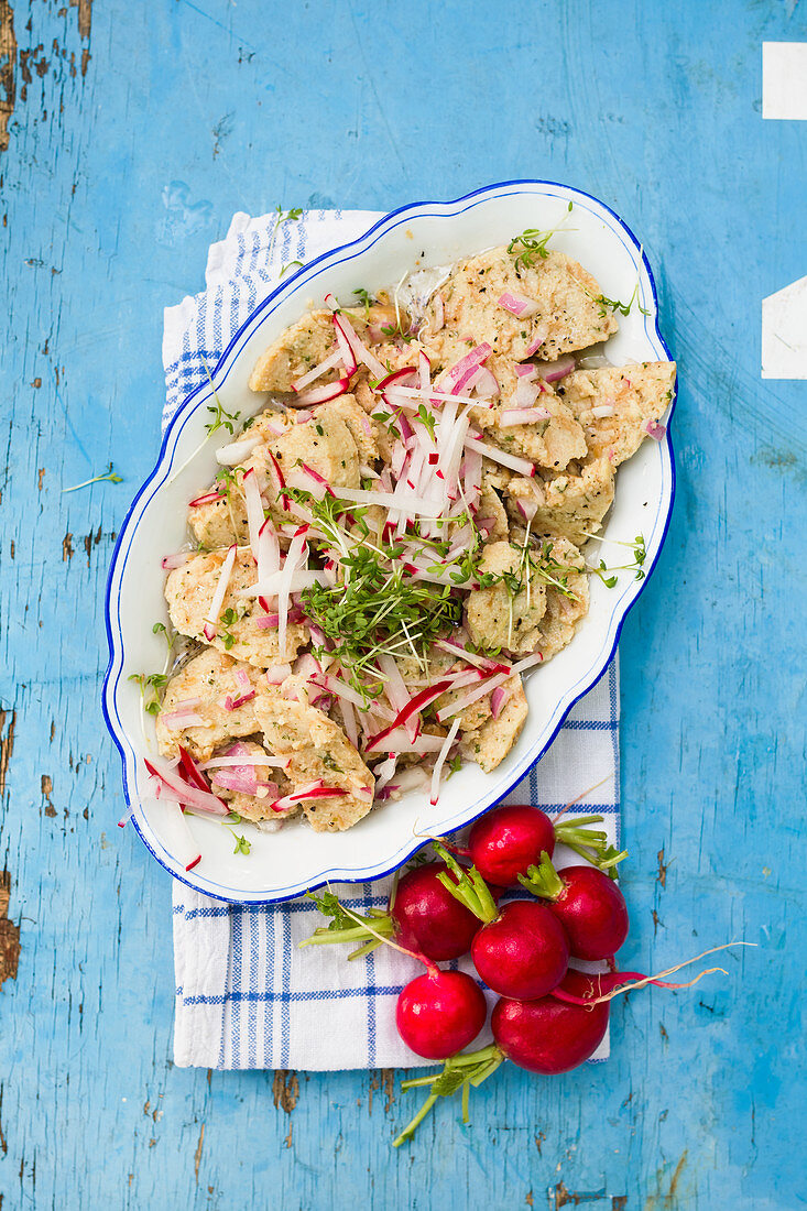 Bread dumpling salad with radishes on a blue wooden table