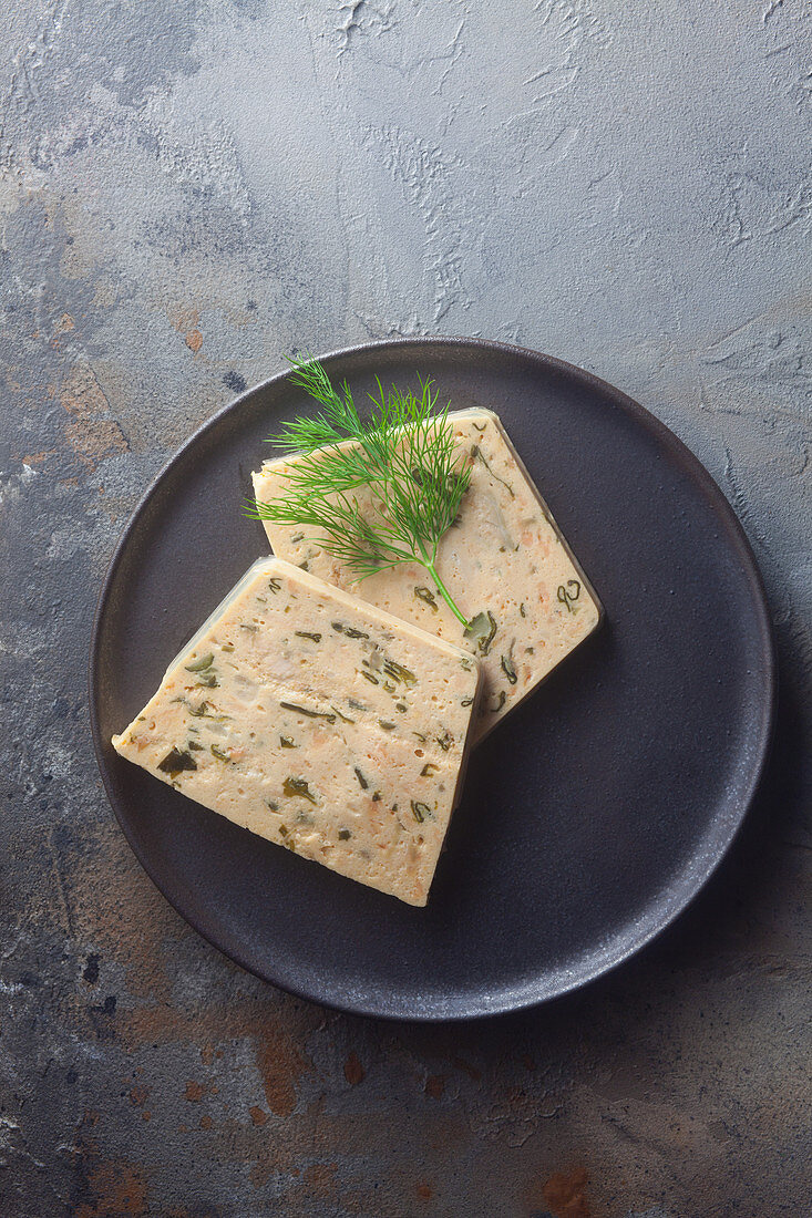 Two slices of salmon terrine with dill on a plate (top view)