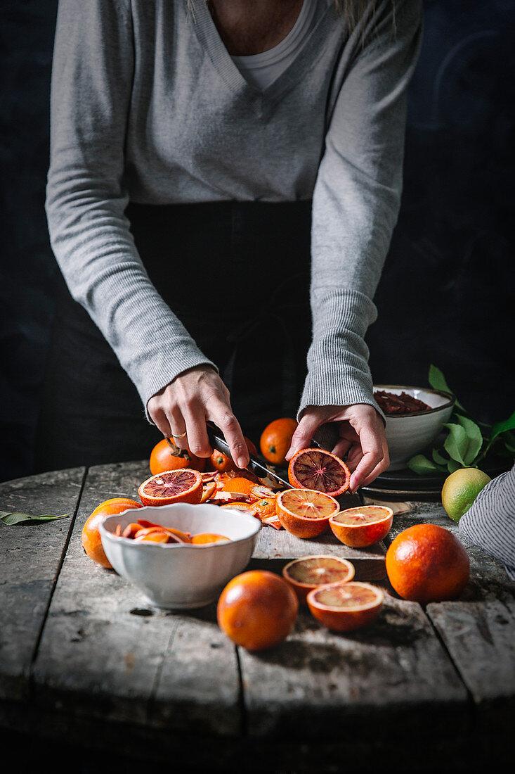 Person peeling blood oranges