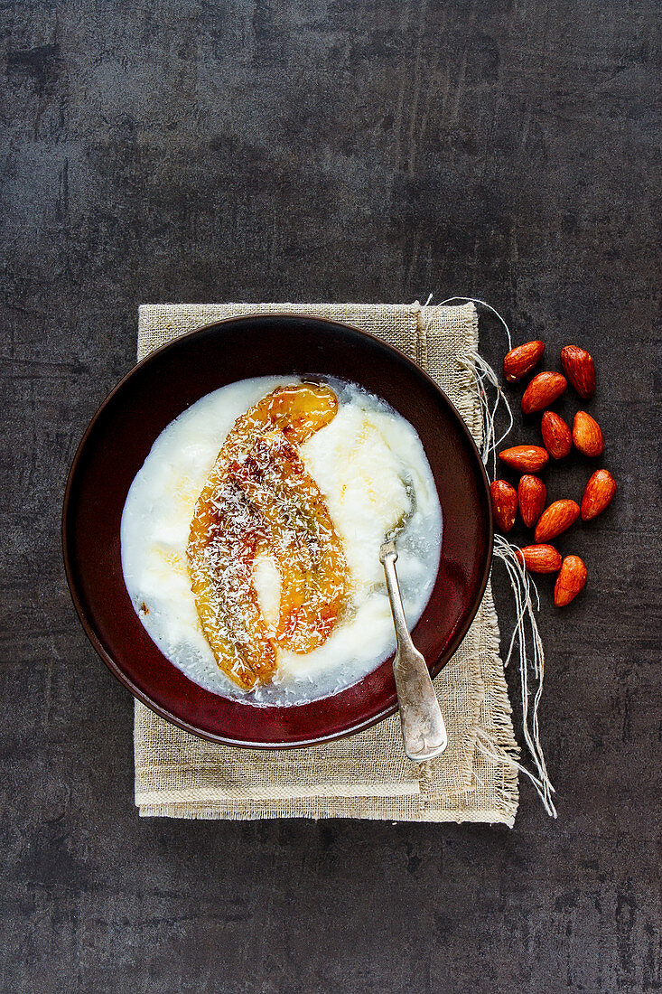 Bowl of greek yogurt with grilled banana, coconut and maple syrup