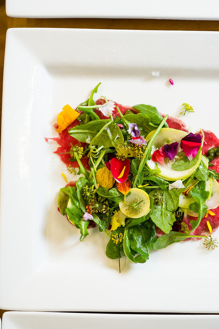 Beautiful greens salad with vibrant edible flowers, squash and light dressing