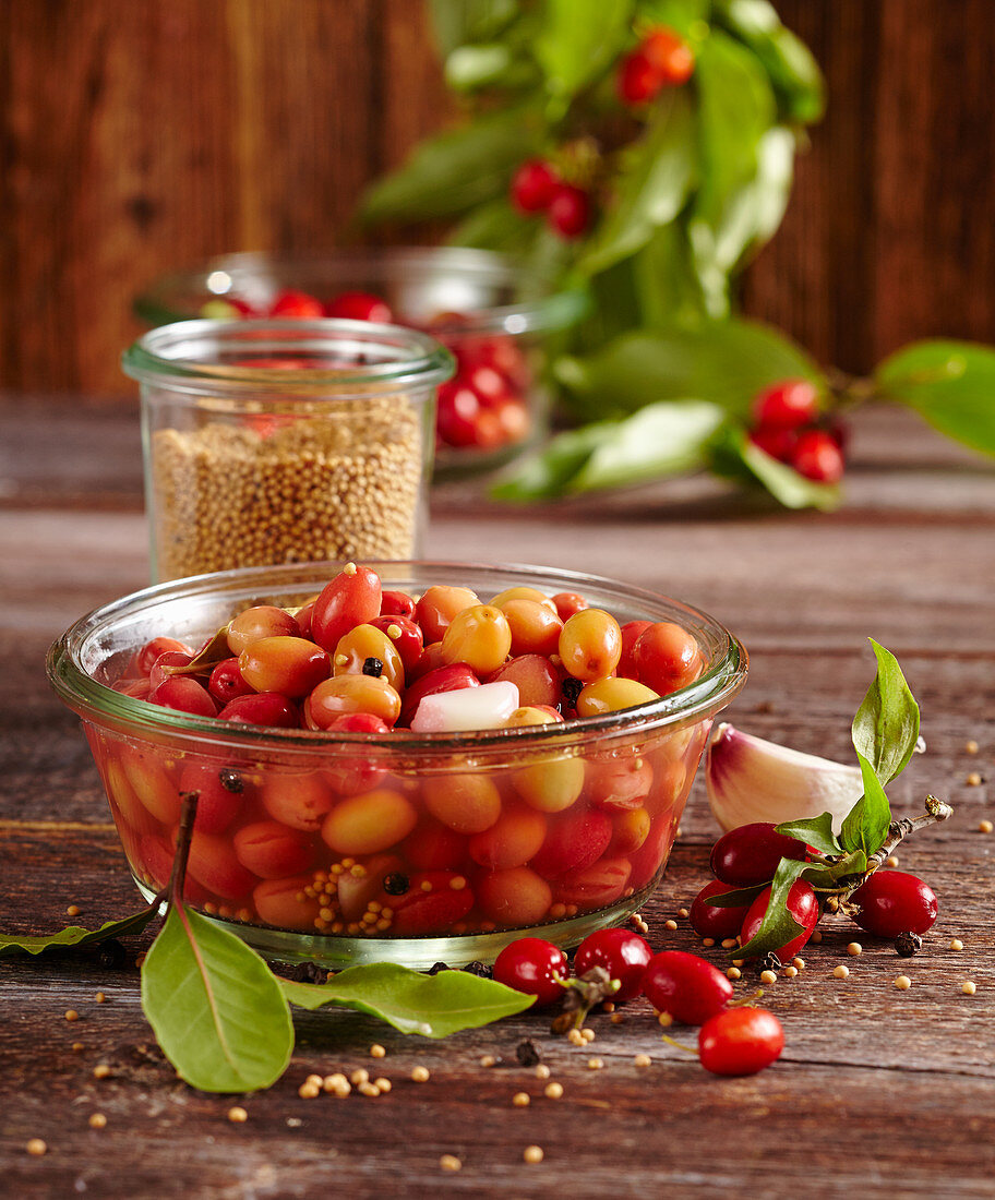 False olives: pickled cornelian cherries in a glass bowl with vinegar, bay leaves, mustard and garlic