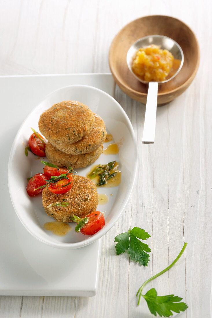 Baked amaranth and cheese rounds with a mango dip and cherry tomatoes