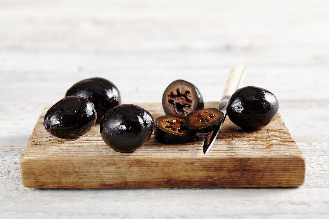 Pickled Johannisnüsse (black nuts) on a wooden cutting board