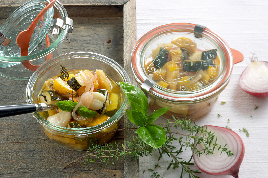 Homemade courgette antipasto with garlic, fresh herbs and vinegar in jars