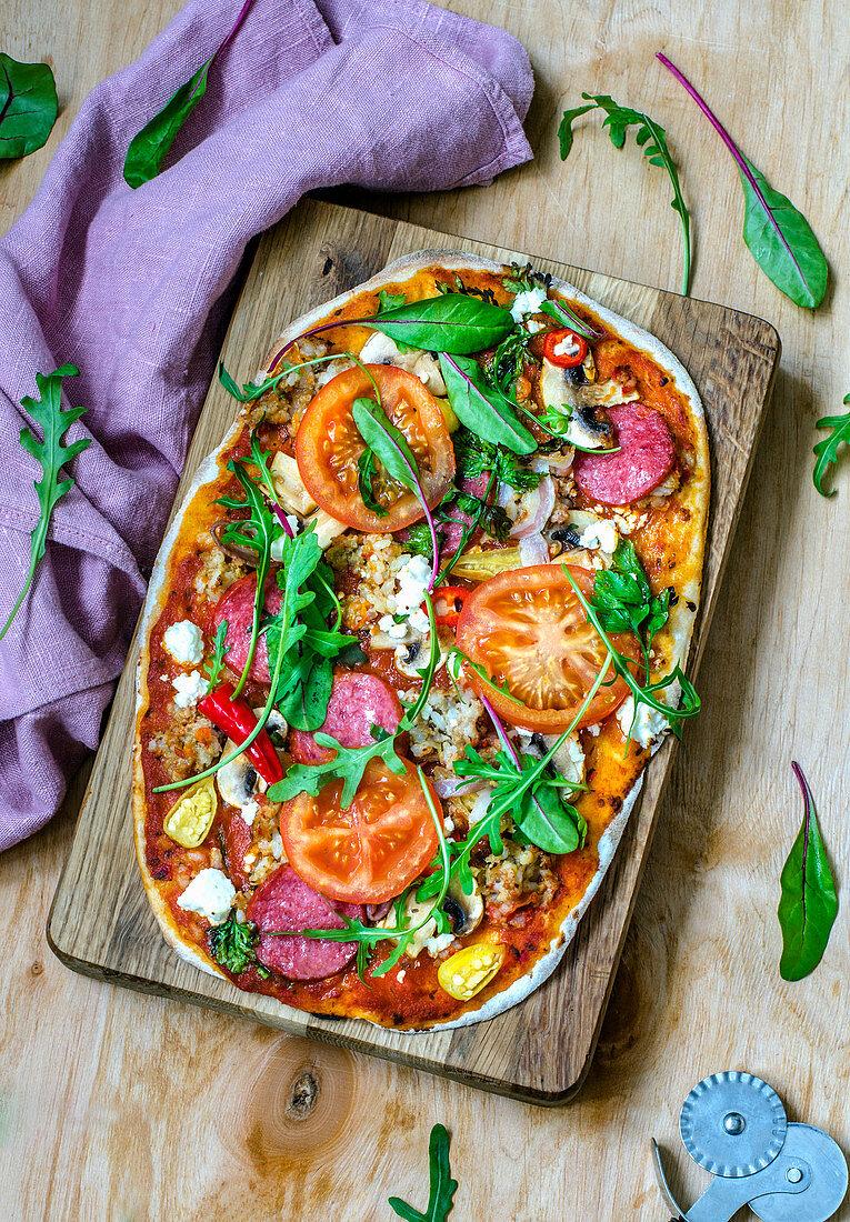 Pizza mit Salami und Gemüse auf Holzbrett