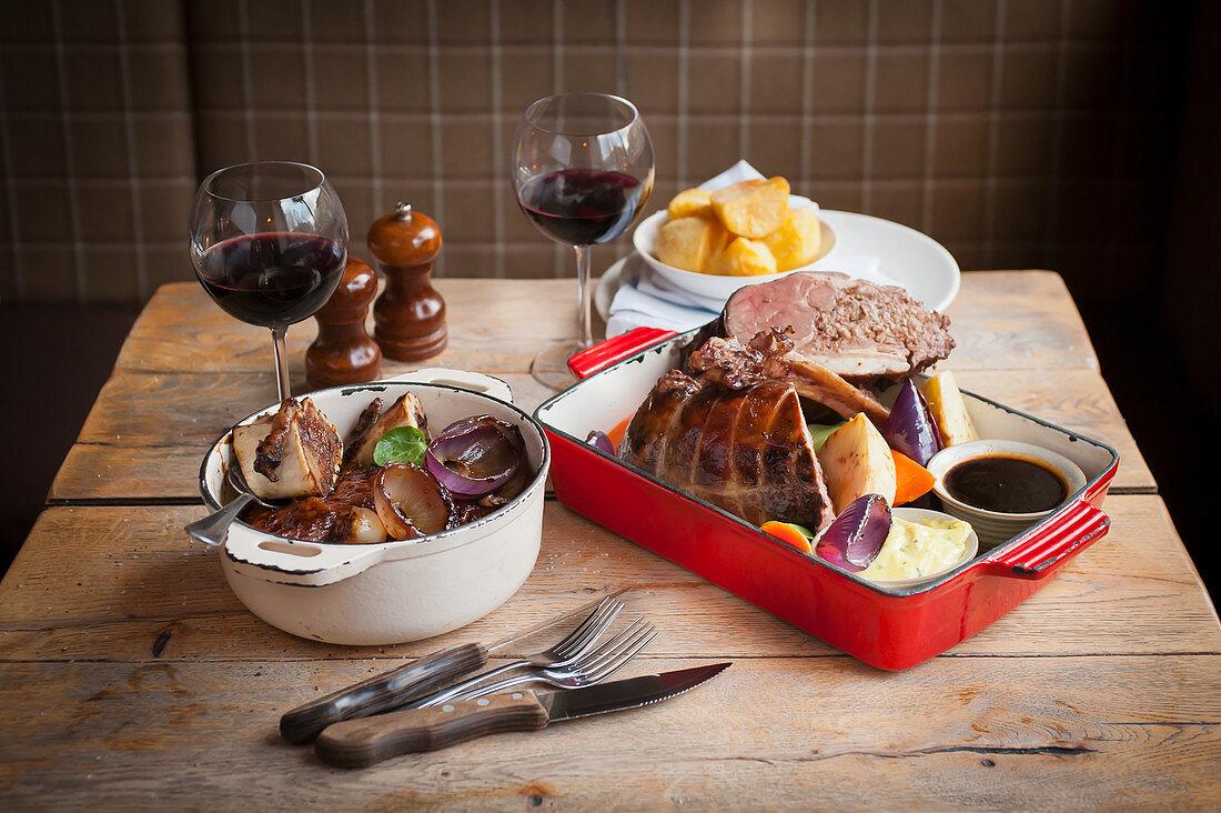 Roast pork and braised marrow bones on a rustic wooden table