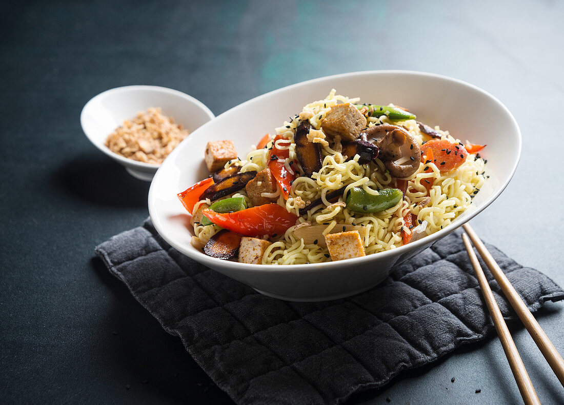 Mie noodles with oriental, stir-fried vegetables and tofu, sesame seeds and roasted onions (vegan)