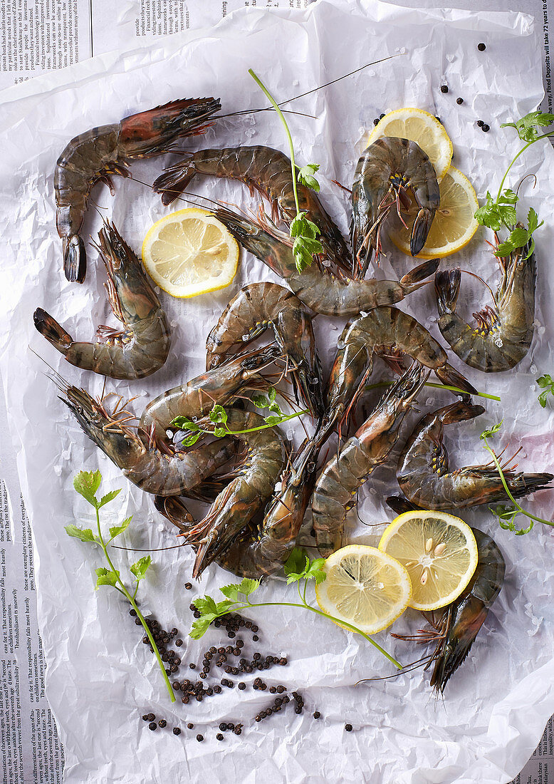 Fresh Tiger Prawns and lemon slices placed on parchment paper