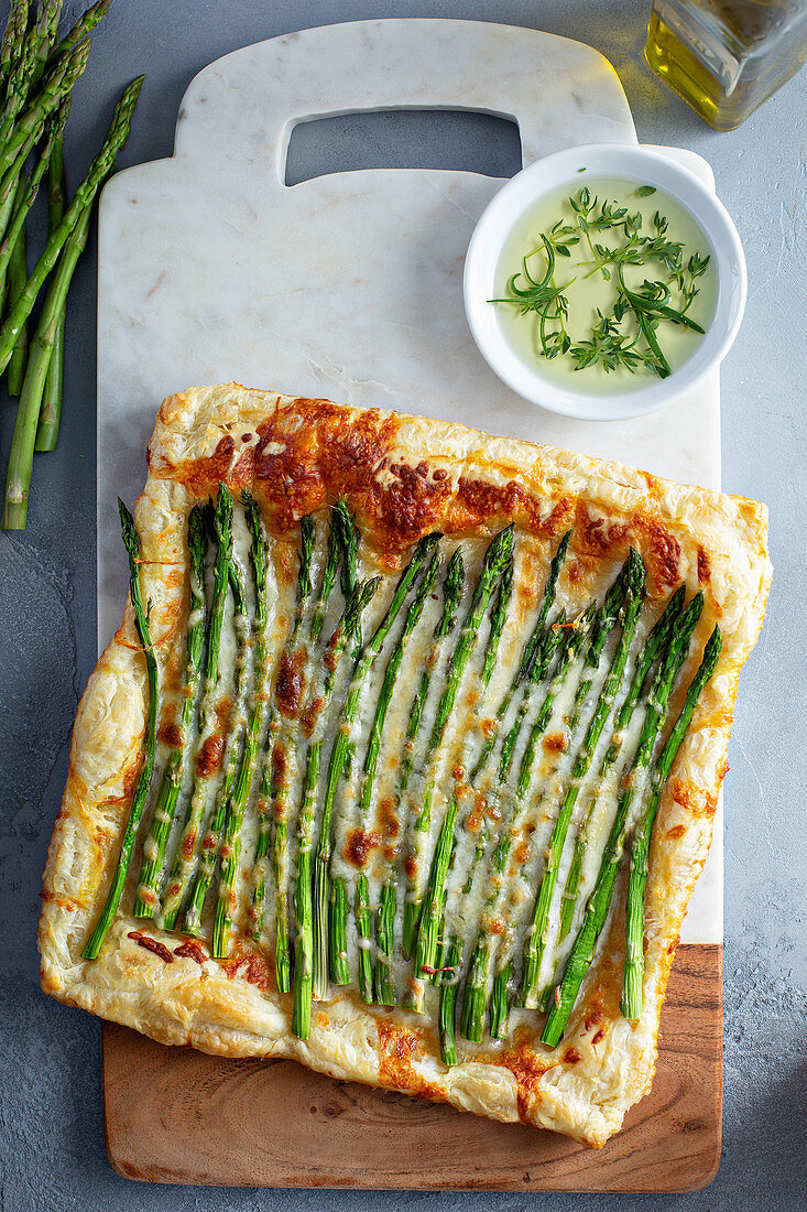 Puff pastry appetizer with cheese and asparagus served with herbs and olive oil