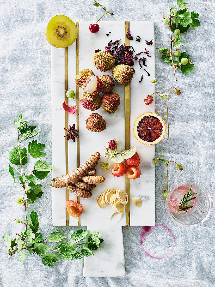 A still life with turmeric, lemongrass and fruit on a white wooden cutting board