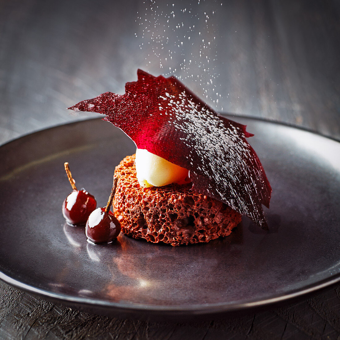 Valrhona chocolate dessert with cherries and icing sugar